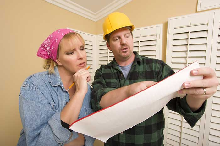 Male Contractor in Hard Hat Discussing Plans with Woman in Room.