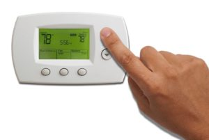 finger pushing button on hvac thermostat