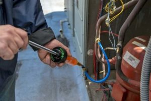 technician performing fluorescent leak detection