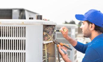 Man wearing blue repairs AC unit