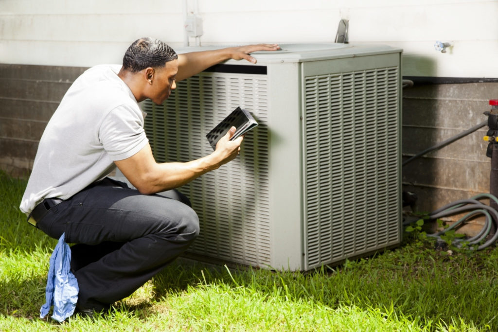 man checks hvac unit for repair