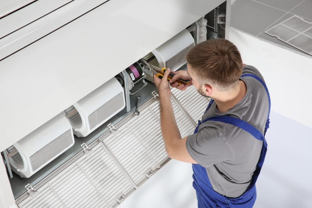 Man repairs white air conditioner
