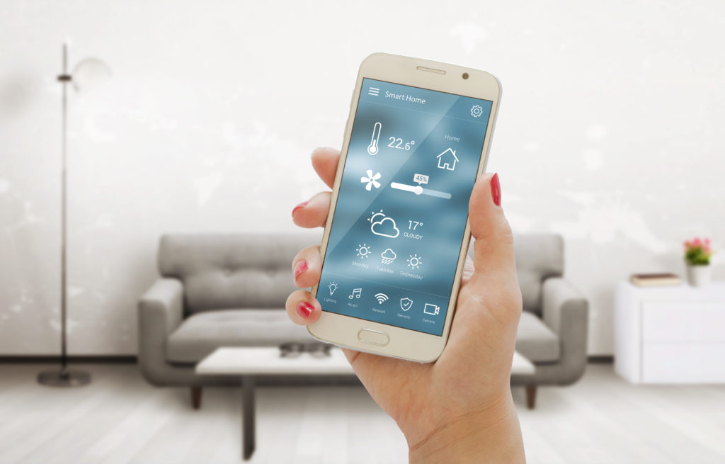 hand holding smartphone with thermostat app in living room