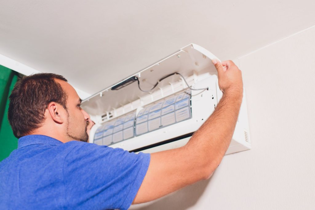 Man repairs wall air conditioner unit
