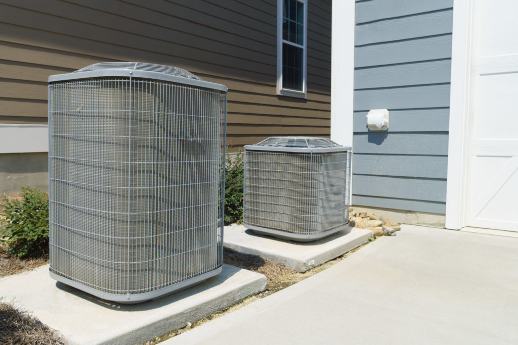 two hvac units outside home with paneled walls