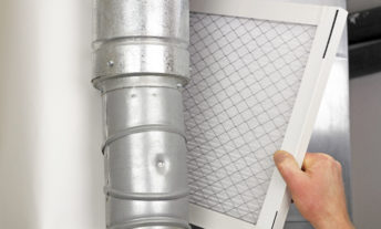 person replacing air conditioner or furnace filter
