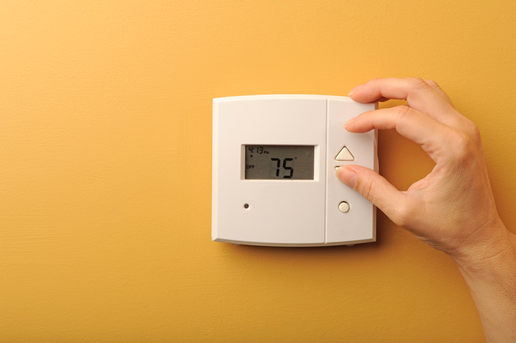 woman-adjusting-thermostat